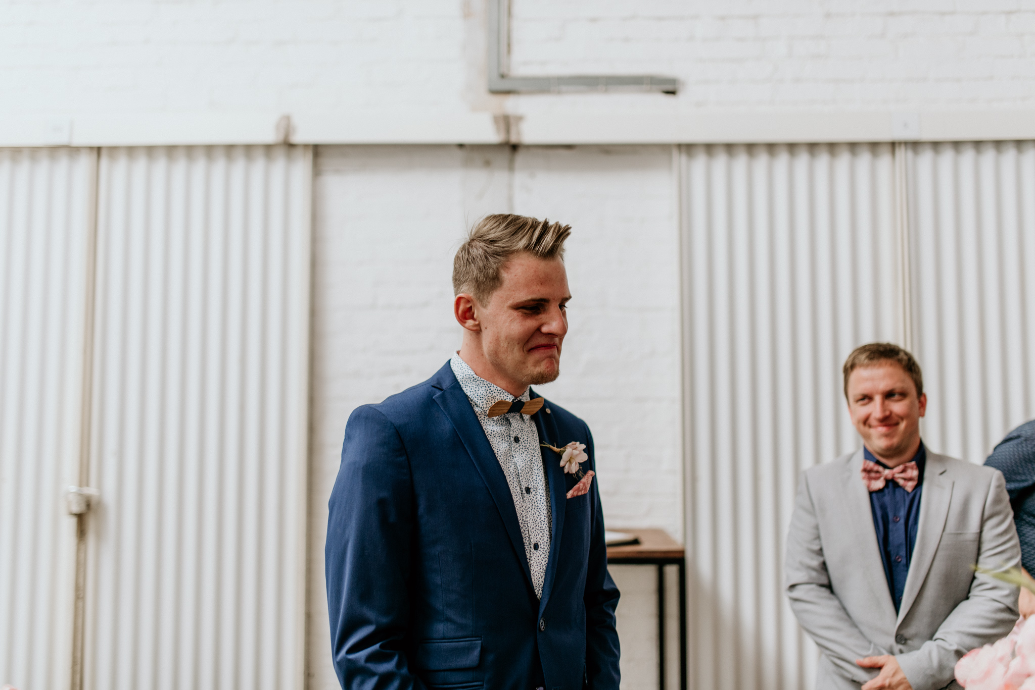 A dapper groom in a blue suit cries as he sees his bride for the first time - by Dillon Kin Photography