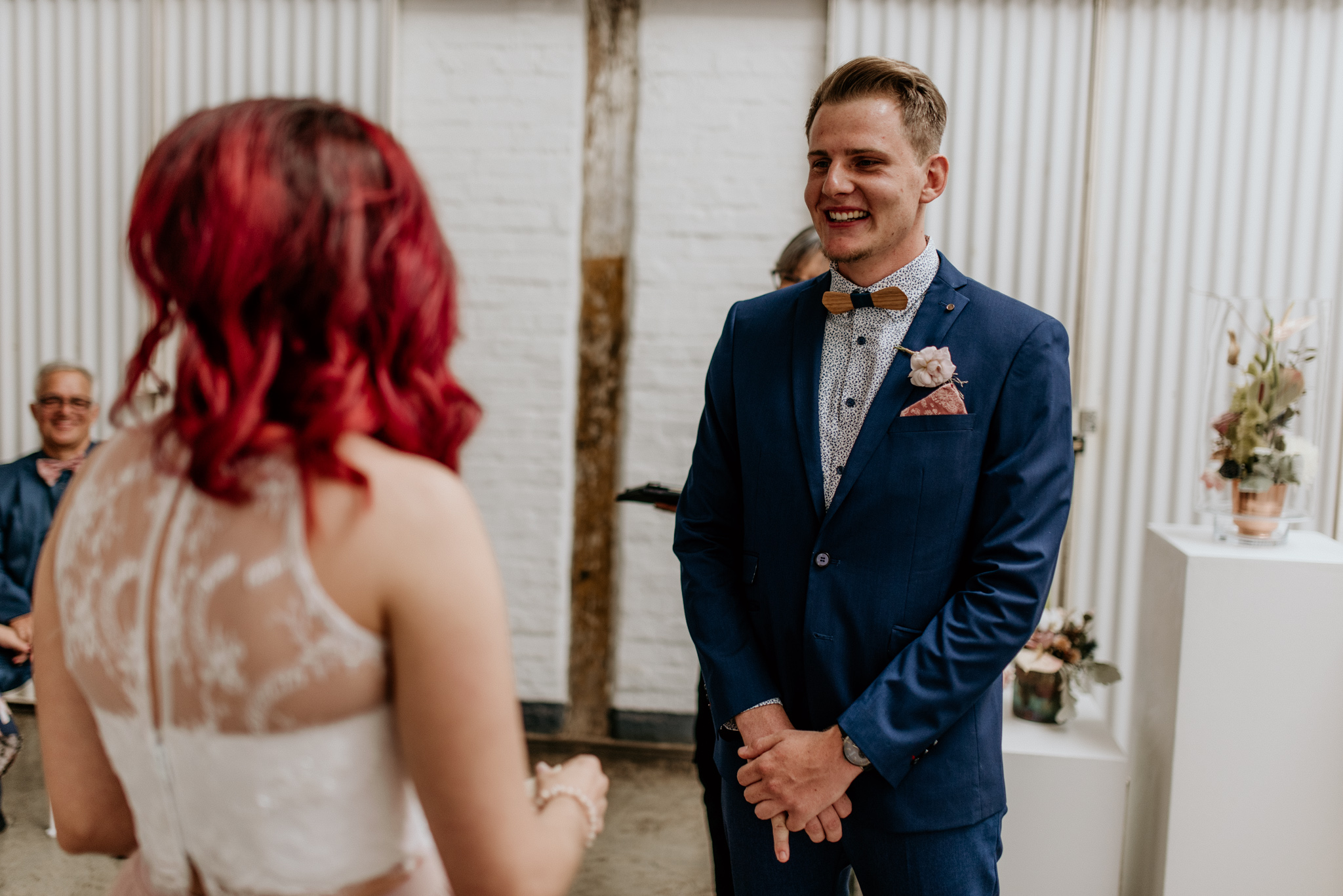 Groom in a blue suit shows big smile as bride reads vows at their maboneng wedding
