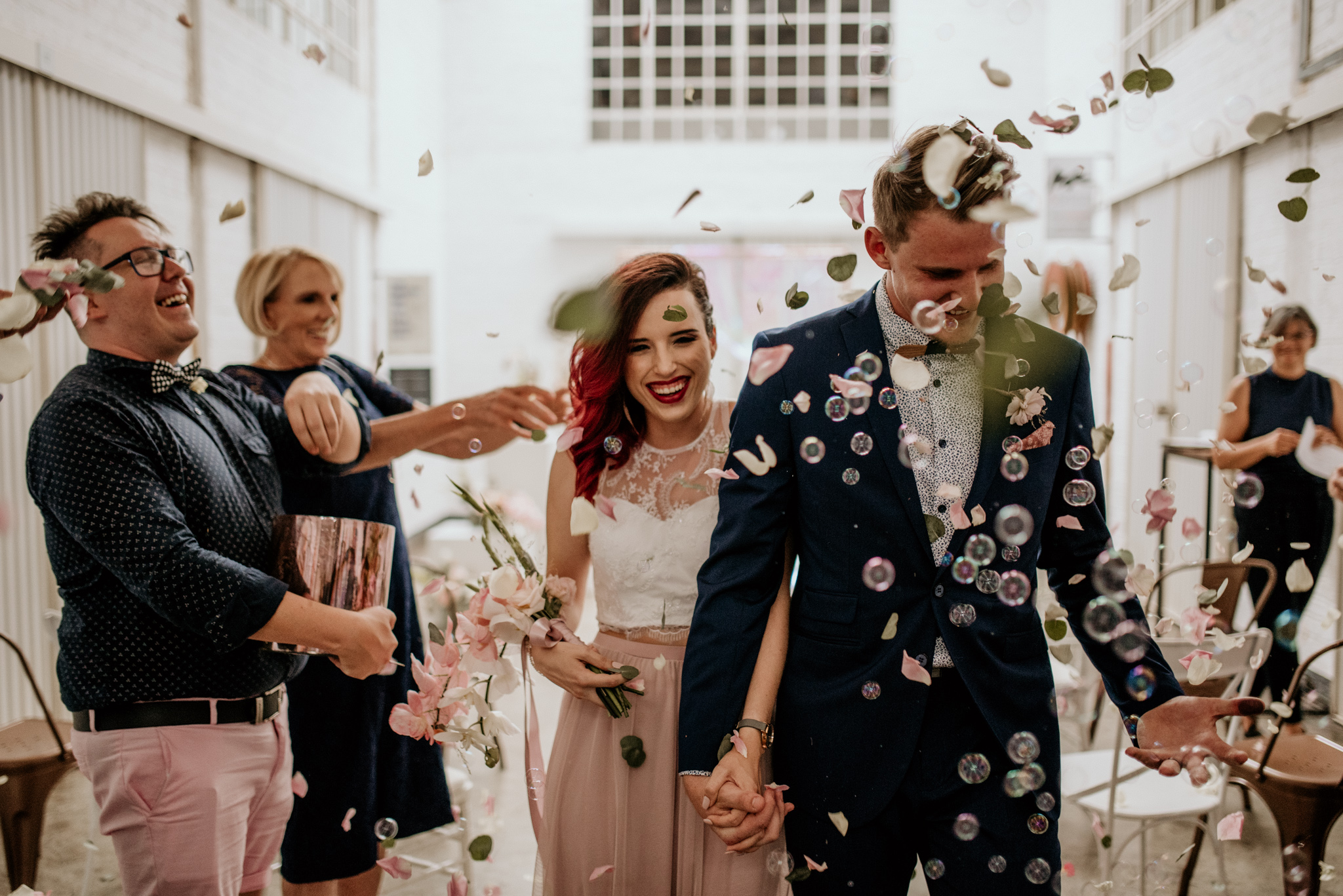 Bride and groom leave the building with bubbles being blown and confetti thrown by guests