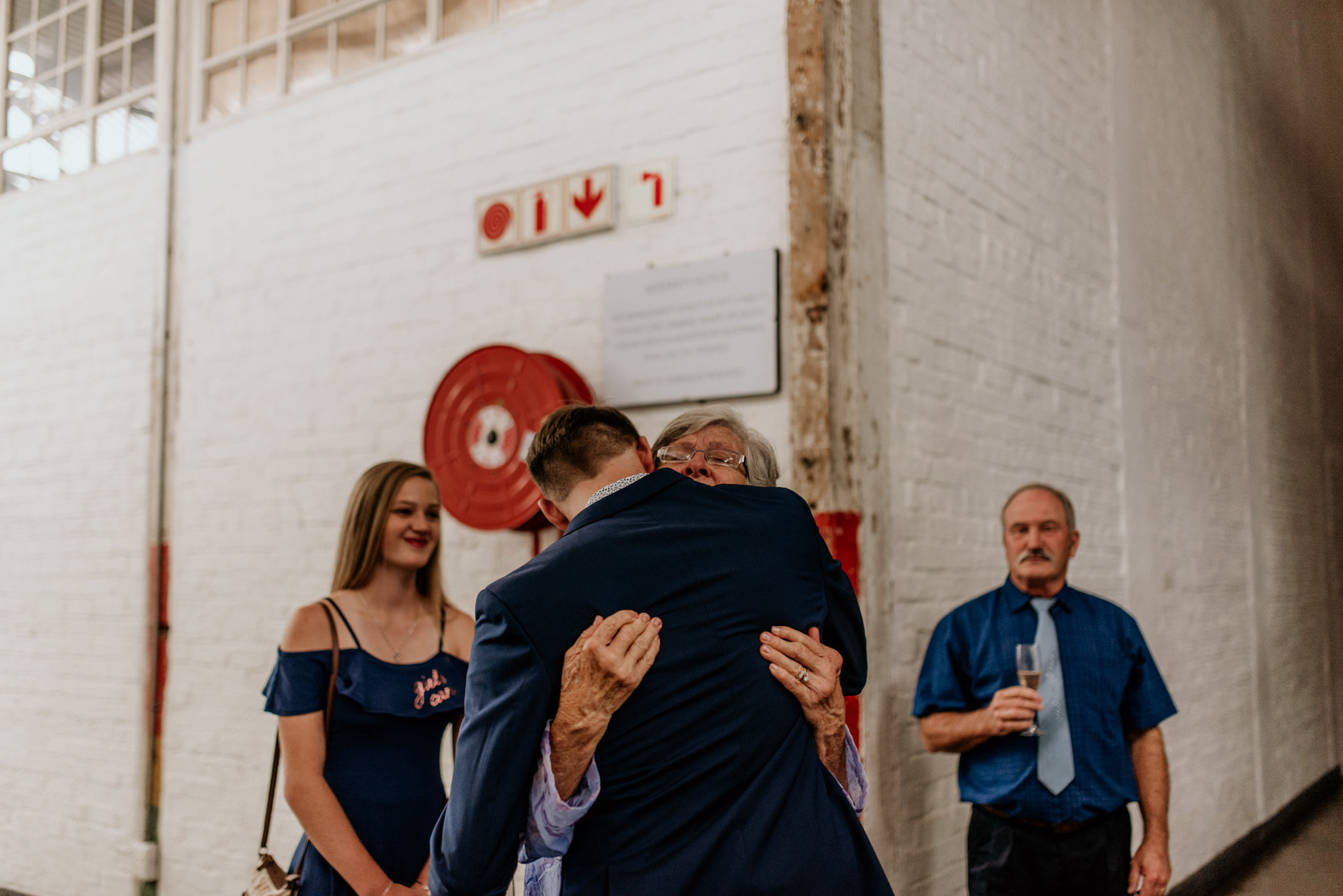 Grandmother embraces a groom in blue suit in Johannesburg wedding
