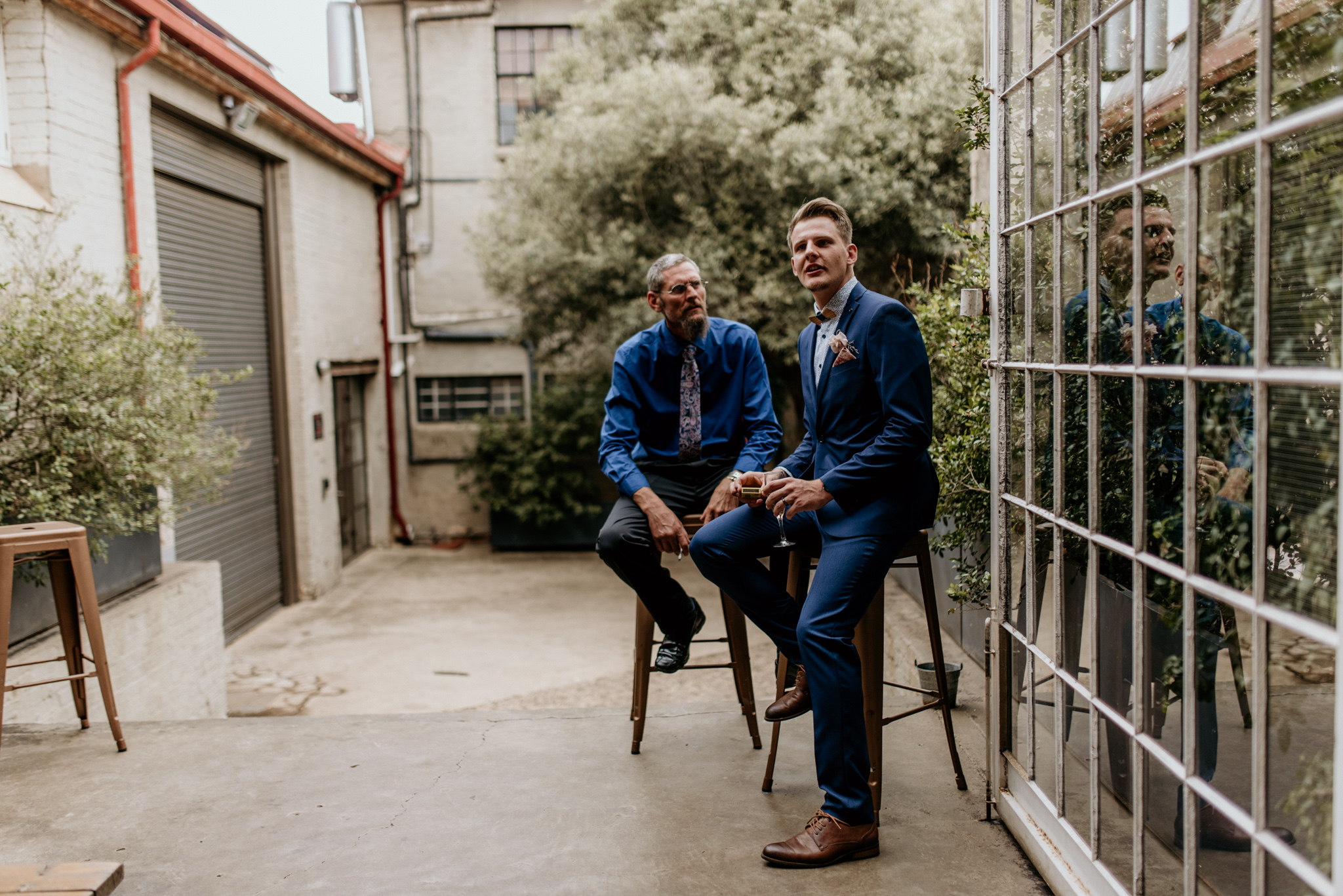 Groom and uncle both in blue suits sit together at a johannesburg city wedding