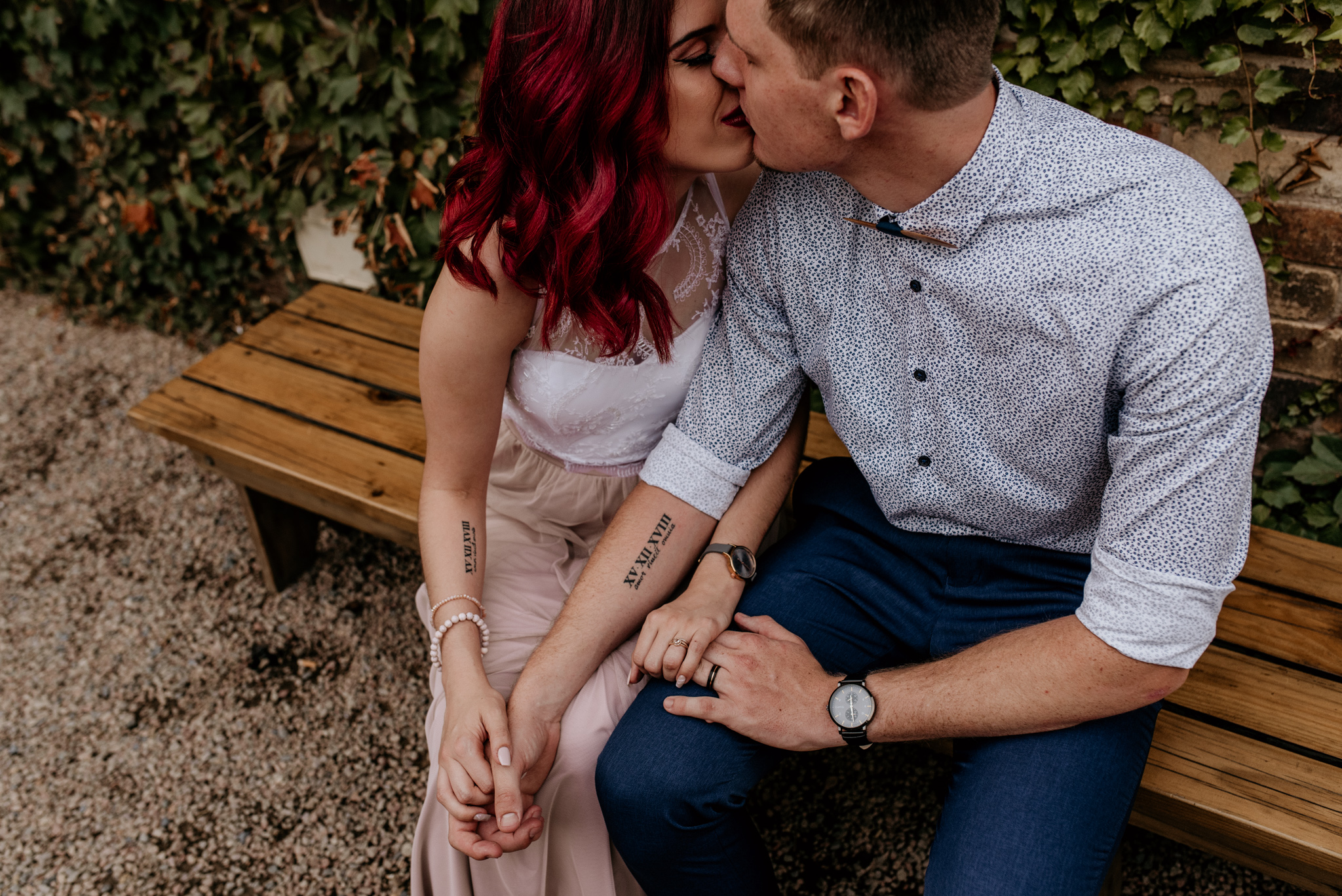 Bride and groom with tattoos on their arms share a kiss after their wedding in Maboneng