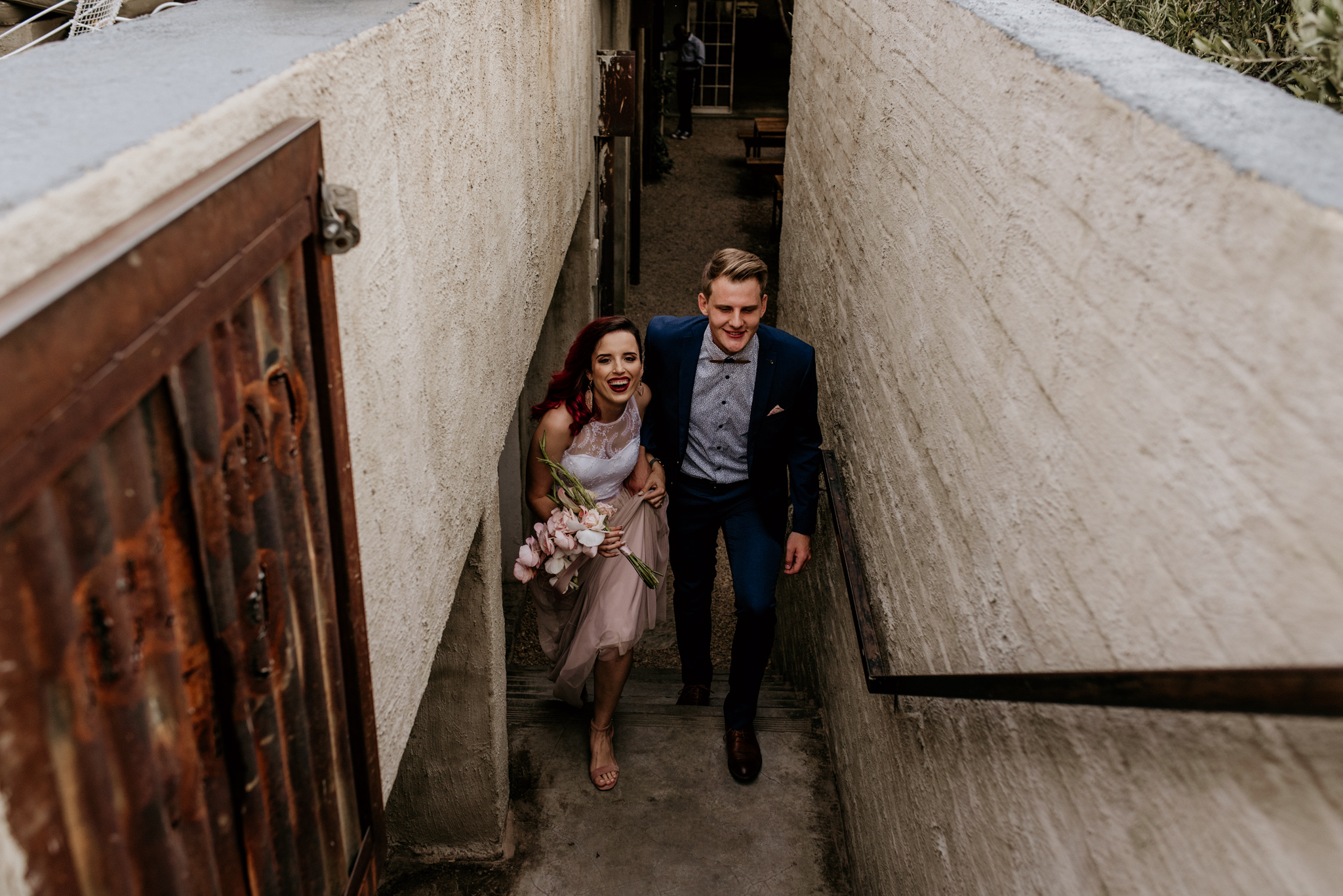 Bride and groom walk up stairs at Arts on Main in Johannesburg after their wedding