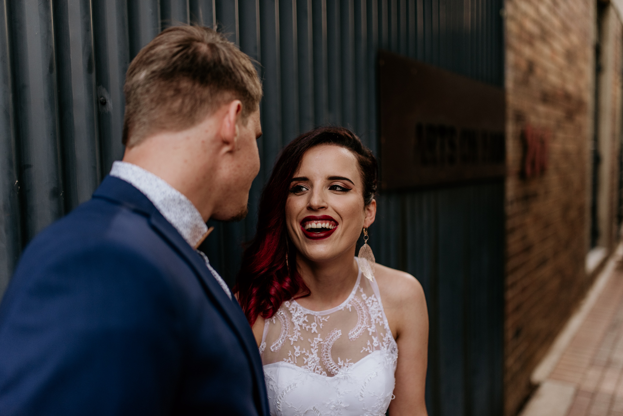 Beautiful young bride with red hair smiles at her new husband in Johannesburg