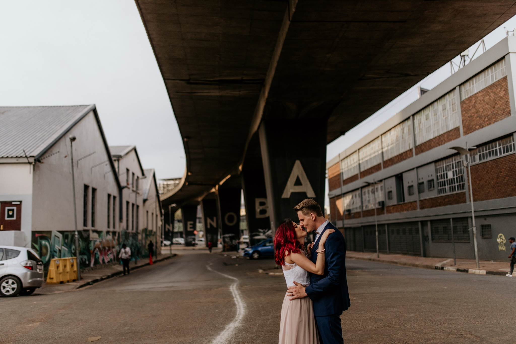 Redhead bride kisses groom in blue suit at maboneng Johannesburg