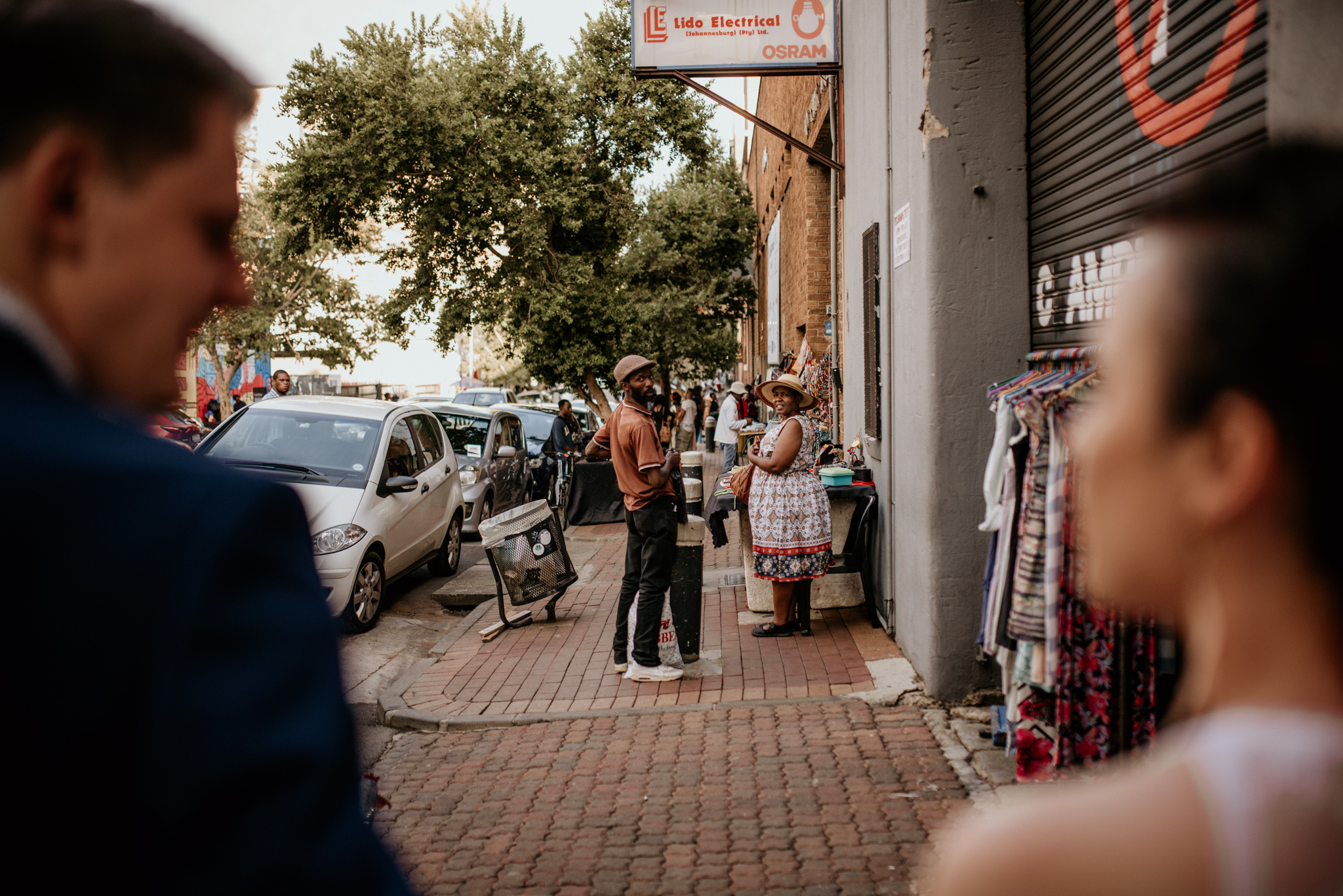 Street vendors look at newly wed couple after their wedding in Johannesburg