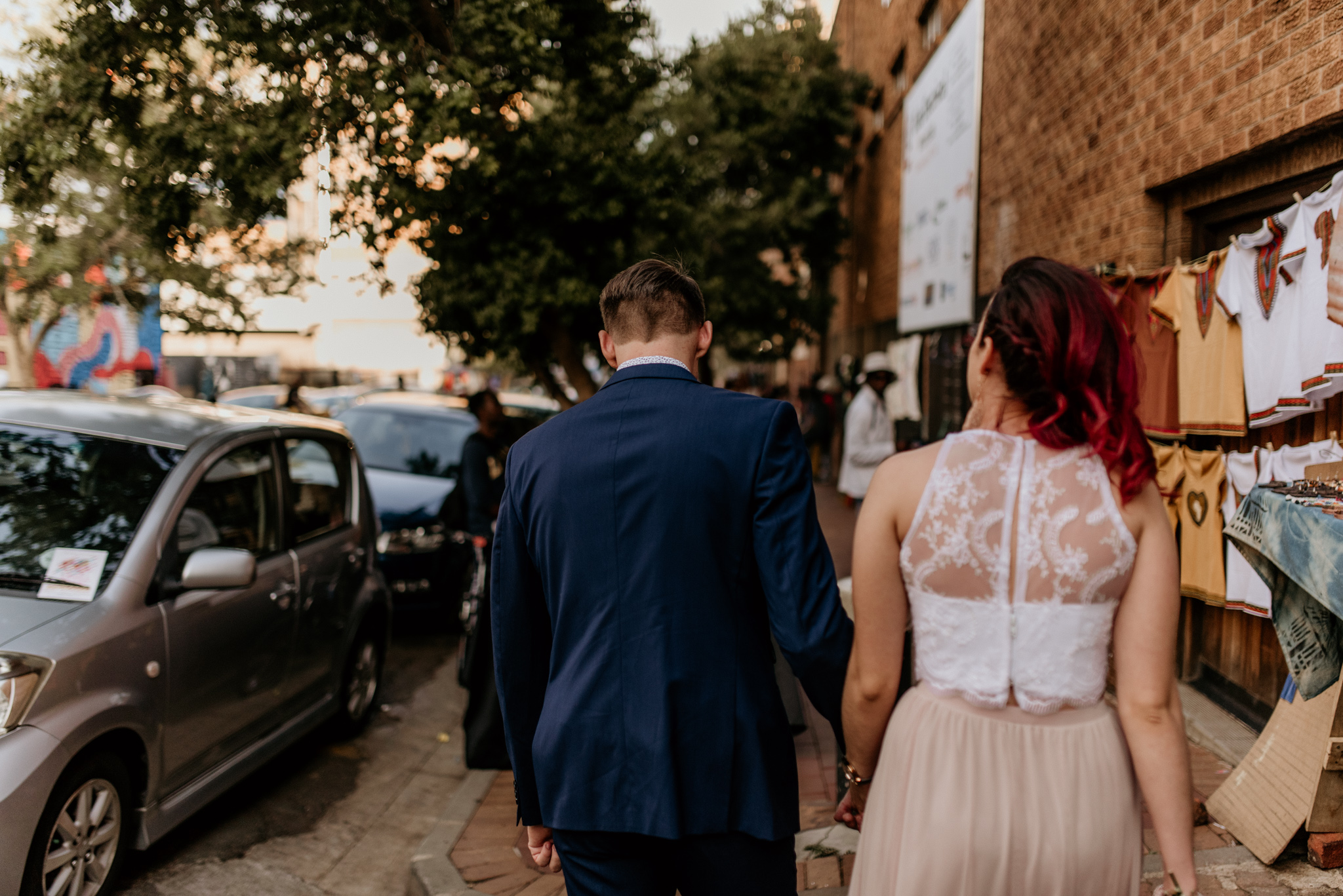 Redhead bride and groom in blue suit walk the streets of Maboneng in Joburg