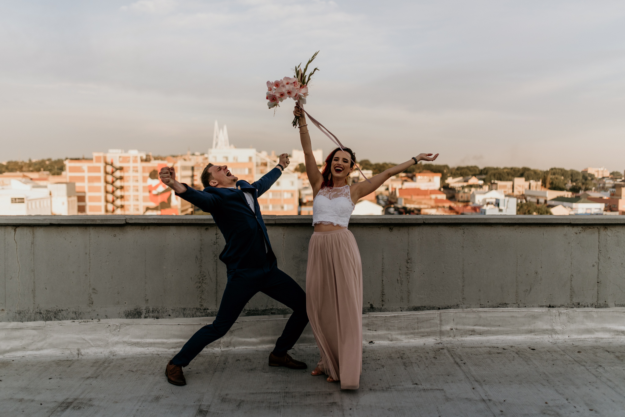 Young trendy couple wave their hand up in joy after getting married on a Johannesburg rooftop