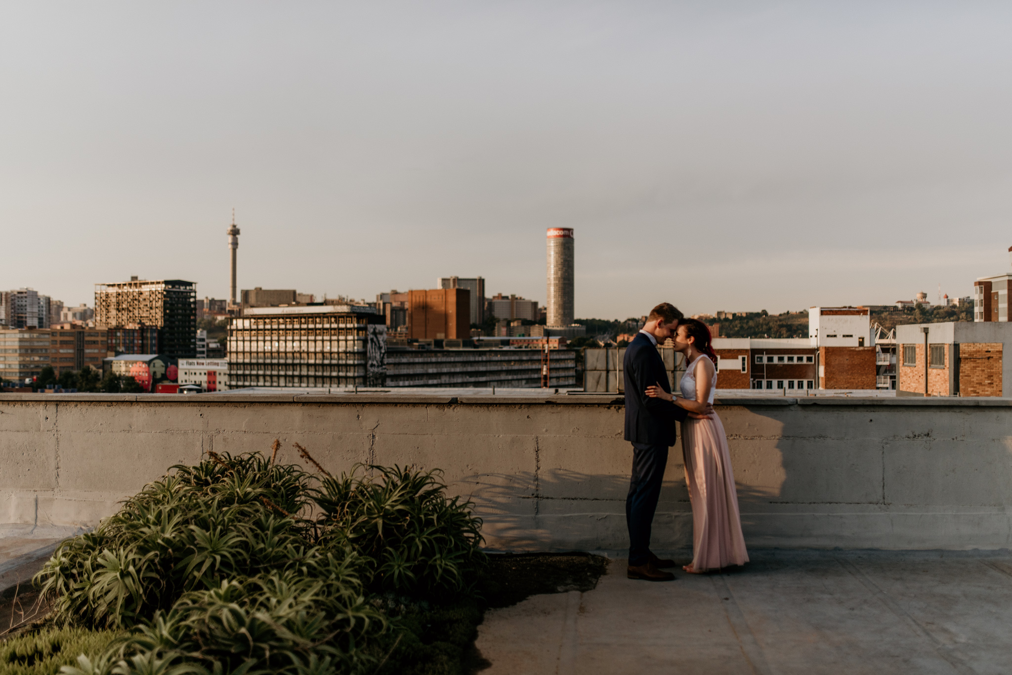 Young trendy married couple embrace each other on a Johannesburg rooftop with a skyline view