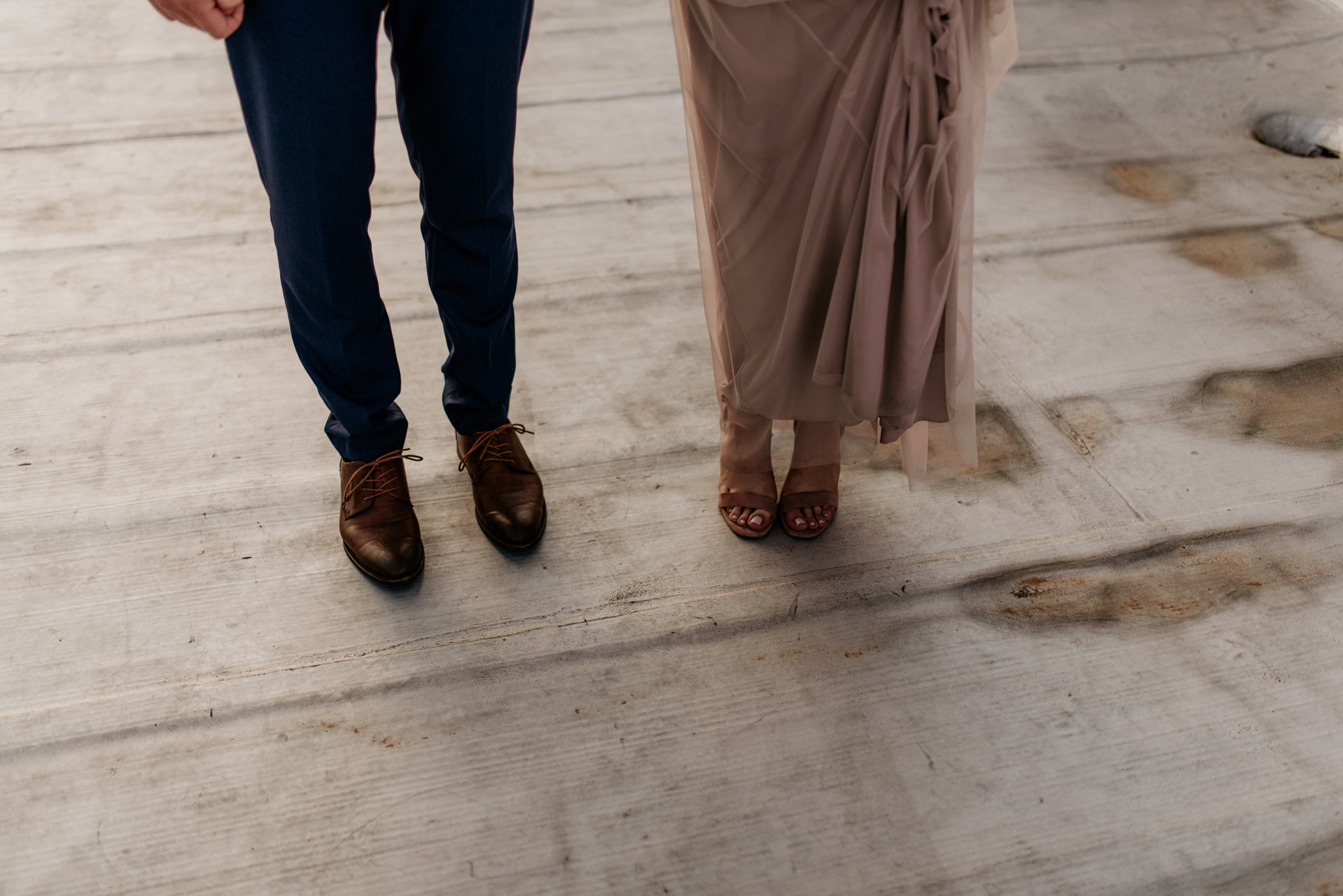 Bride and groom stand together showing off their wedding shoes