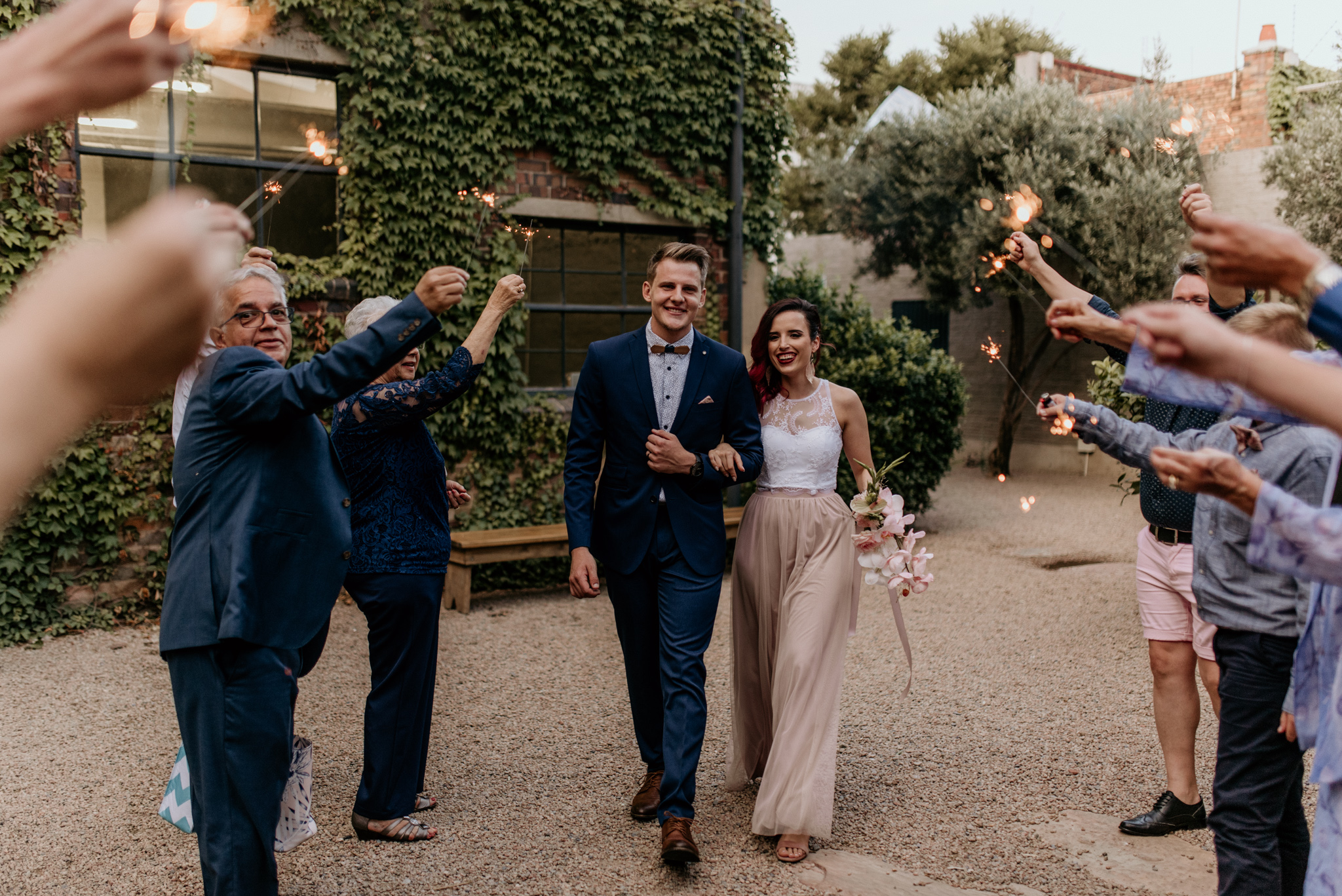 Bride and groom walk through as guests hold up sparklers at their johannesburg wedding
